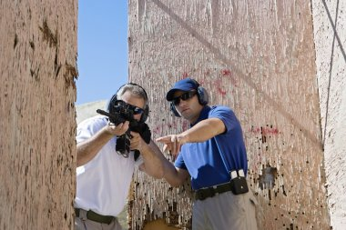 Instructor Assisting Man With Machine Gun
