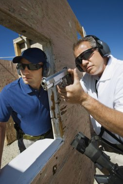 Instructor Assisting Man With Hand Gun