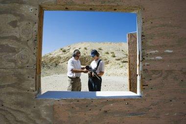 Instructor Assisting Woman At Firing Range In Desert