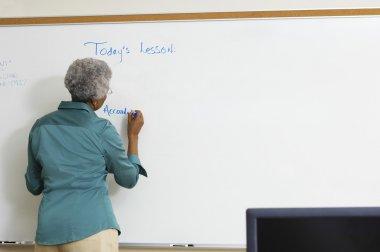 senior teacher writing on the whiteboard