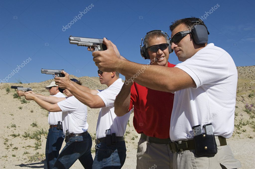 Happy instructor assisting officers with hand guns at firing range during weapons training stock vector