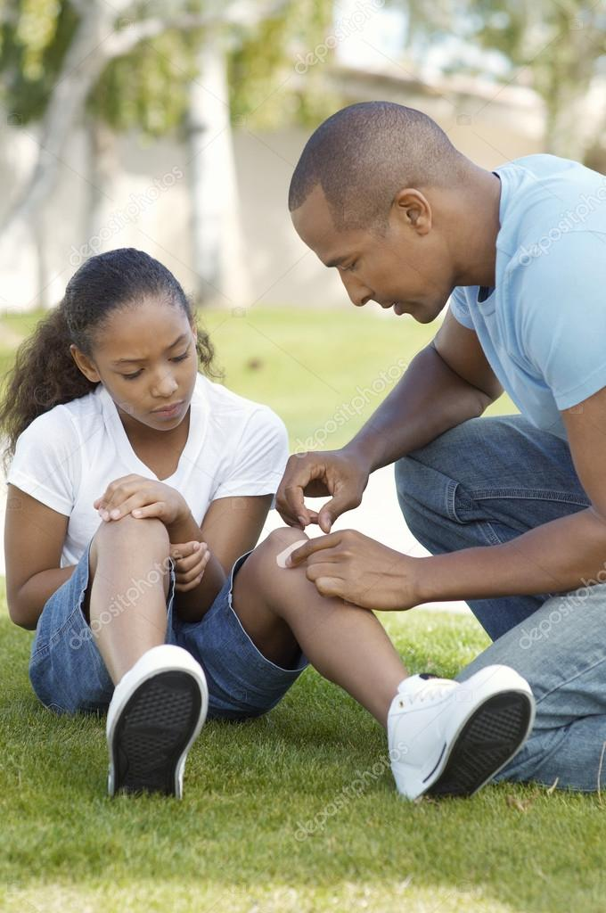 Father Applying Bandage On Daughter's Knee