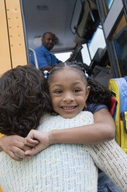 girl hugging mother over school bus