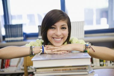 Female Student With Stack Of Books In Library