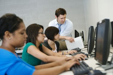 Teacher Helping Students In Computer Lab