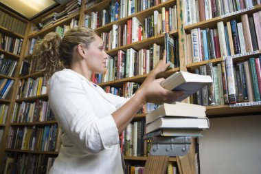 Young female librarian with books