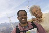 Fotografie Mature Couple With Map By Wind Farm