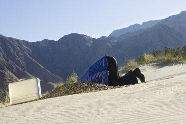 Businessman Burying Head In The Sand