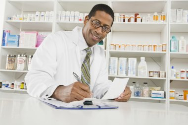 Male Pharmacist Working In Pharmacy