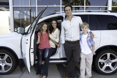 Happy family next to white car