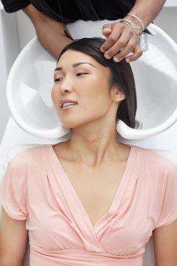 Asian woman having hair wash at beauty salon