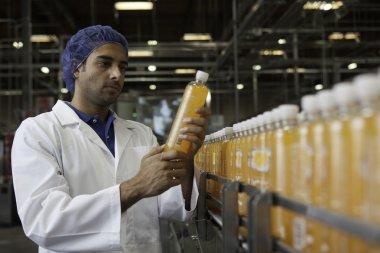 Worker examining juice at bottling plant