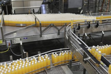 Orange juice bottles on conveyor belt