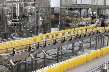 Orange juice bottles on conveyor belt in bottling plant stock vector