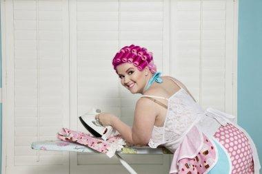 happy curvy woman ironing