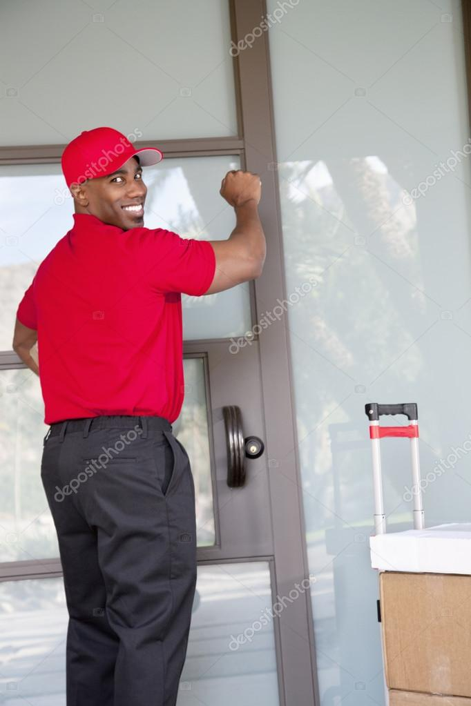 Young delivery man with packages looking back while knocking on door u2014 Stock Photo & Young delivery man with packages looking back while knocking on door ...