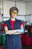 portrét šťastný mechanik nosit ochranné vybavení s rukama zkříženýma v garáži auto opravy