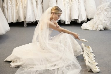 Side view of young woman in wedding dress confused while selecting footwear