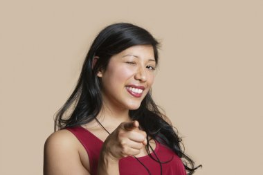 Portrait of a young woman pointing while winking over colored background
