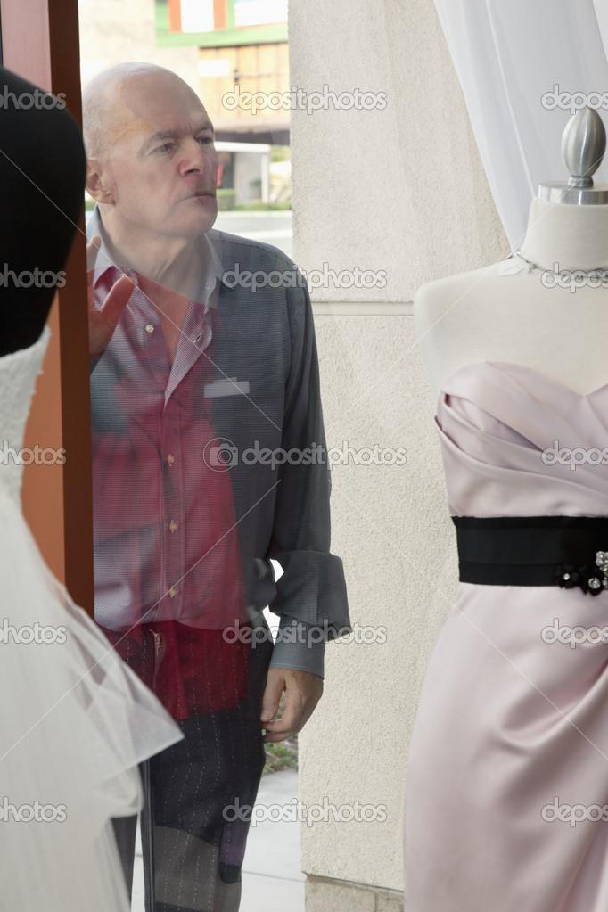senior hombre mirando vestido de novia aparece en la ventana en la