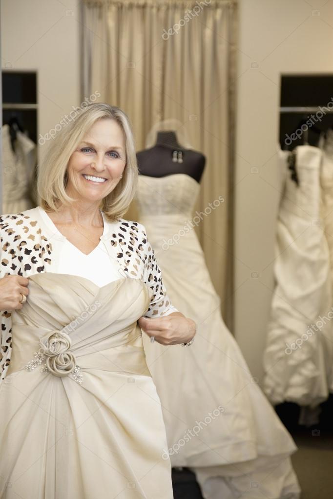 Retrato de una mujer mayor feliz con vestido de novia en tienda ...