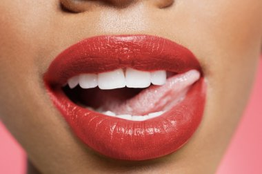 Cropped image of woman licking red lipstick