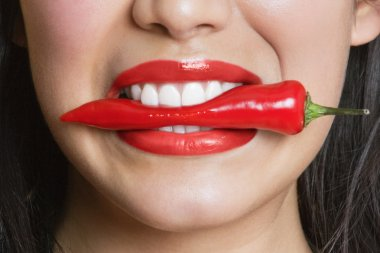 Close-up portrait of Hispanic woman biting red pepper stock vector