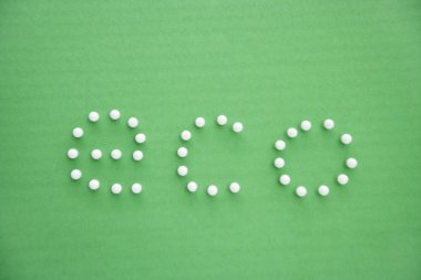 Close-up of push pins spelling eco over green background stock vector