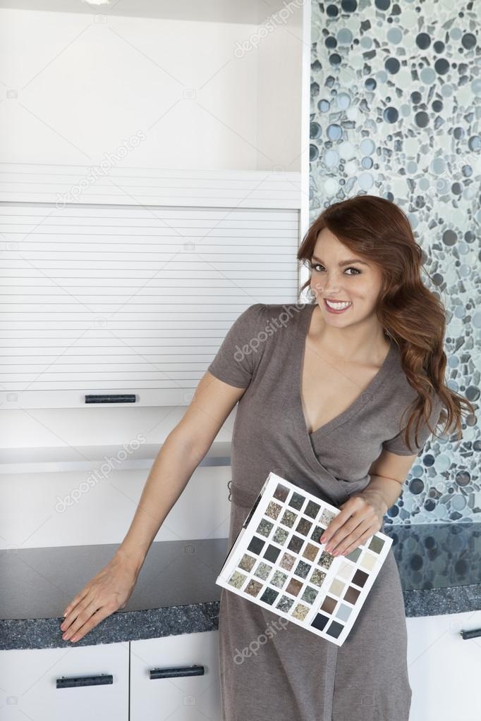 Porträt von schöne junge Frau mit Farbmuster stehen in der Küche ...