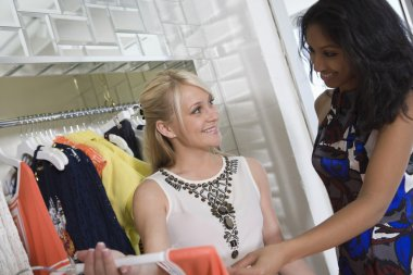 Shop Assistant Helping Customer At Clothes Shop