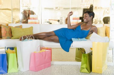 Woman Lies With Shopping Bags In Store Seating Area