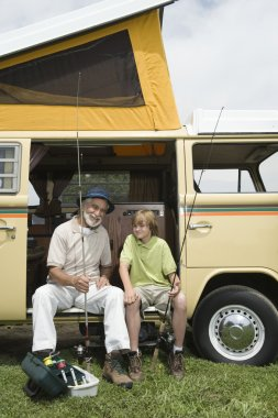 Grandfather And Grandson With Fishing Rods In Campervan