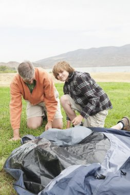 Father And Son Setting Up Tent