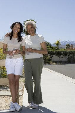 Mother And Daughter Stands On Pavement In Sportswear