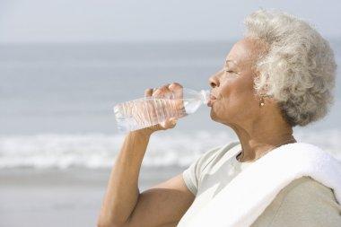 Senior Woman Drinking Water At Beach