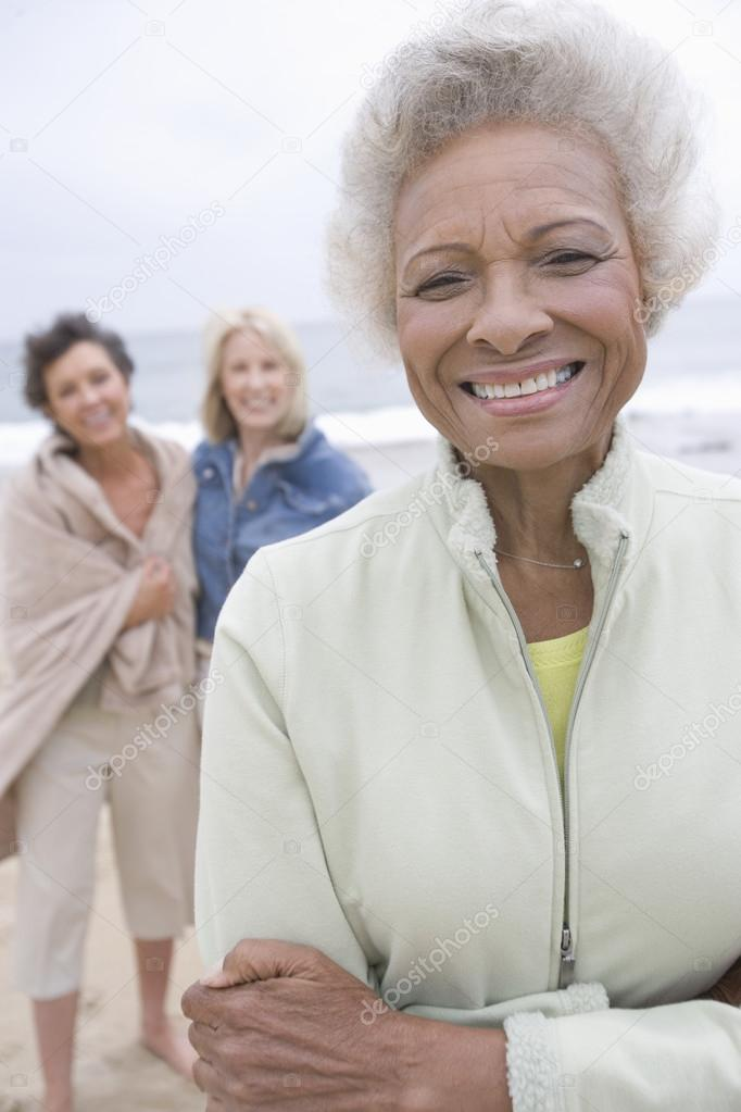 Senior Woman Stands In Fleece Jacket With Friends On Beach