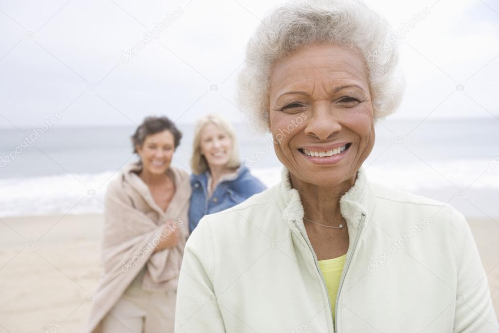 Senior Woman In Fleece Jacket With Friends On Beach