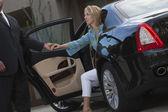 Chauffeur hilft Frau beim Aussteigen aus Auto