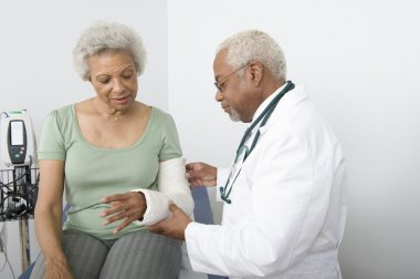 Doctor Checking Patient's Fractured Hand