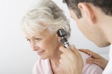 Doctor Examining Patient's Ear Using Otoscope