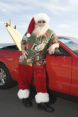 Father Christmas By Convertible With Surfboard