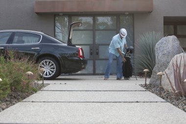 Man Lifting Golf Bag Into Boot Of A Car