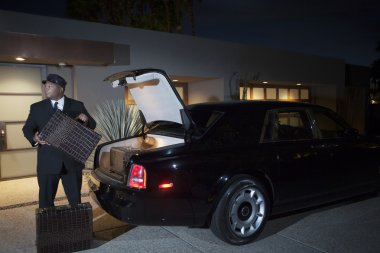 Chauffeur Loading Suitcases In Car