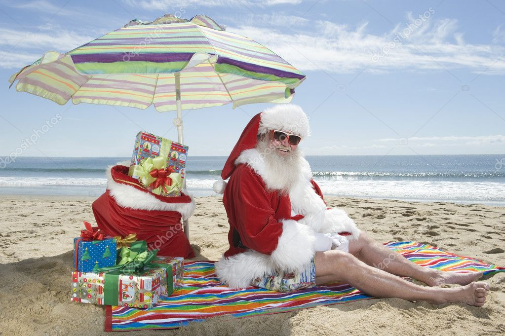 Santa Claus Sitting Under Parasol With Gifts On Beach