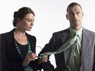 Female Executive Cleaning Glasses On Tie Of Businessman