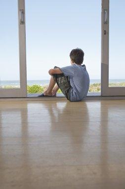 Boy Sitting In Doorway