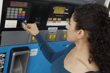 Woman Using Credit Card To Pay For Gasoline