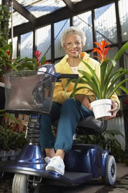 Disabled Woman On Motor Scooter With Plant At Botanical Garden