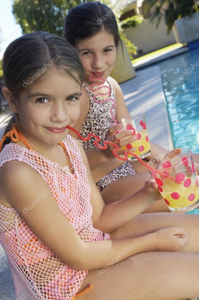 78562f9e Chicas bebiendo el jugo por el borde de la piscina — Foto de stock ...