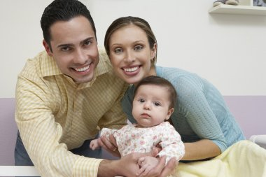 Portrait Of Parents With Baby At Home
